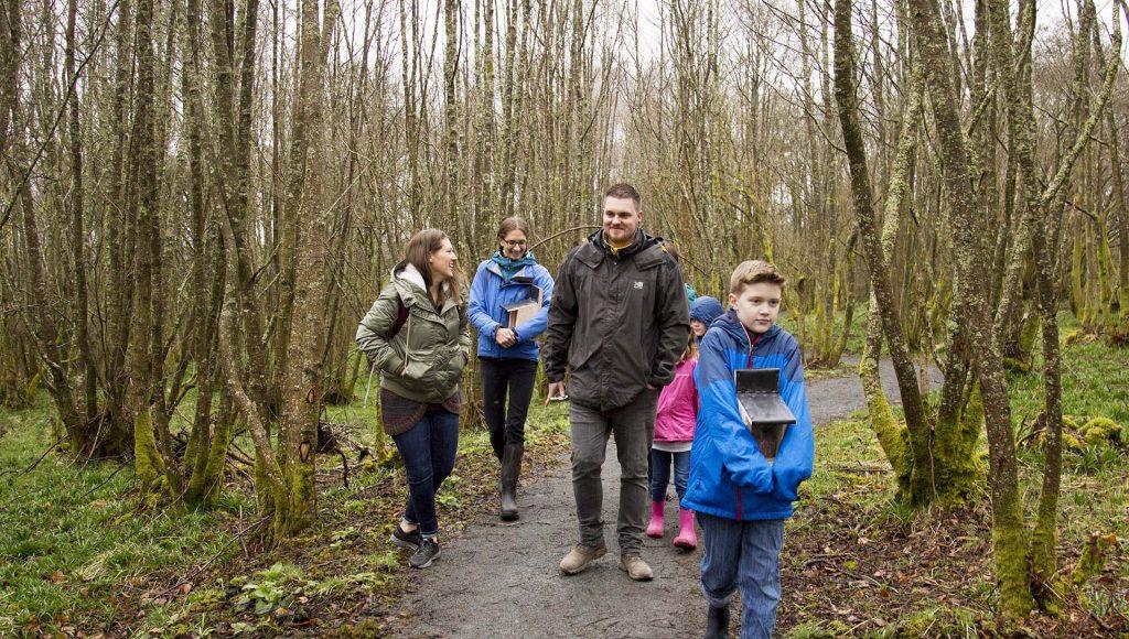 Smiling family walking through woodland, boy ahead carrying feeder box