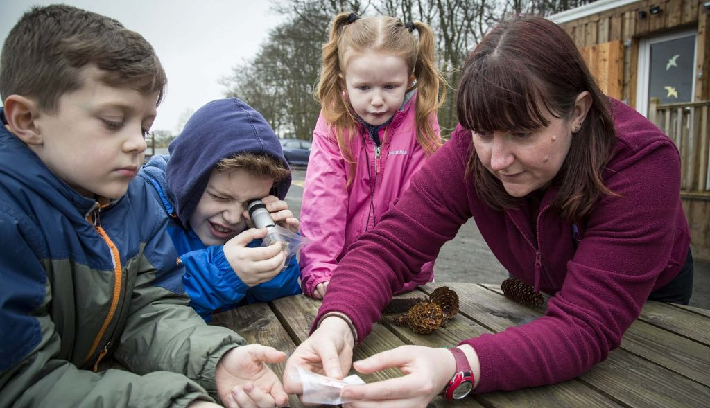 SSRS Conservation officer shows three children how to look at hair samples under a mini microscope