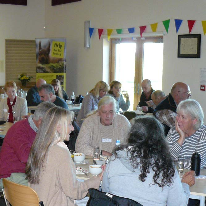 Around 15 people gathered around tables in a hall with colourful bunting on the wall above