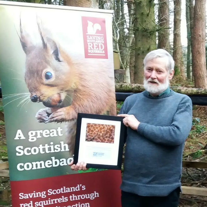 Man holds framed certificate while standing in front of a red squirrel roller banner in woodland