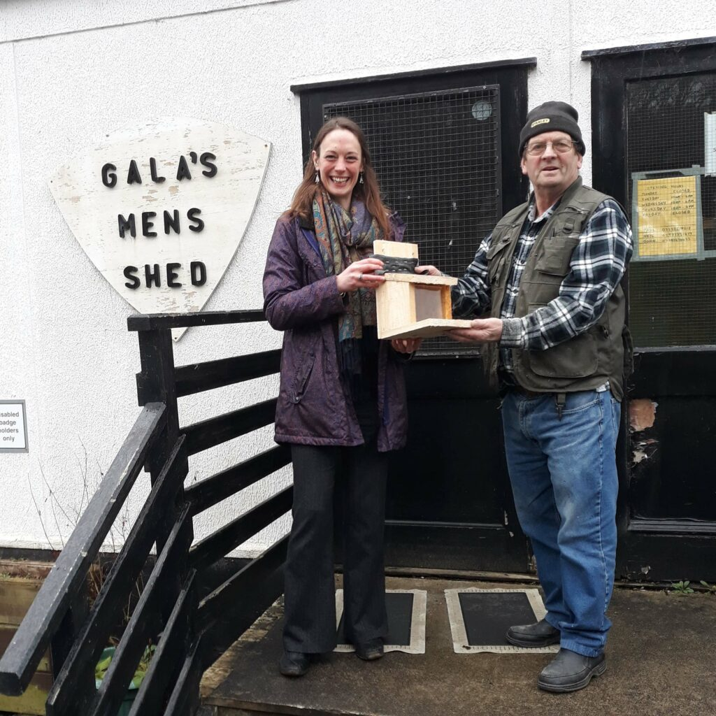 Man presenting feeder box to Alexa outside Men's Shed